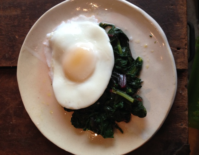 pan-poached egg on bed of beet greens